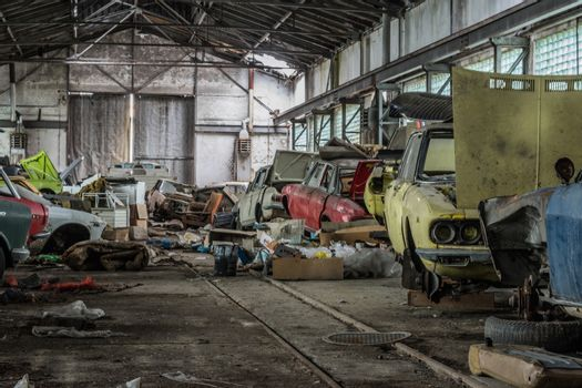Colorful disassembled cars in an abandoned hall
