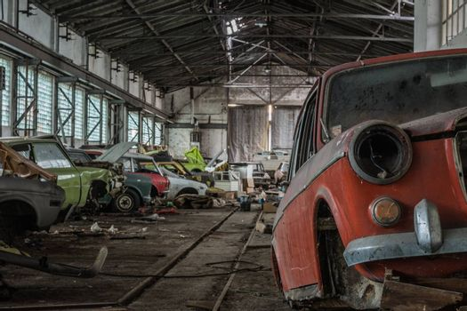 lots of colorful old cars in a hall of an abandoned car repair shop