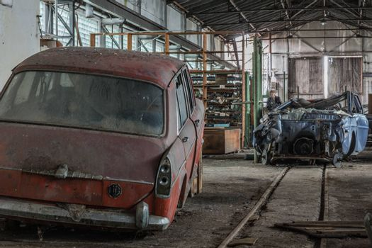 Red old car in a hall of an abandoned workshop