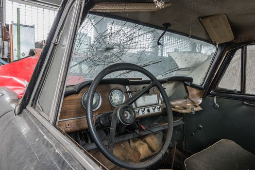 steering wheel and cracked windshield in a car workshop