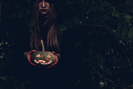 Portrait of woman ghost horror her have pumpkin on hand in forest, halloween day concept