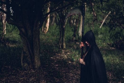 Woman horror ghost holding reaper in forest, halloween concept