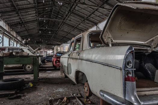 old car with open trunk in a large abandoned hall