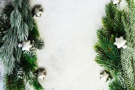 Christmas card concept - frame made with evergreen  tree branches with snow and baubles decor on stone background with copy space