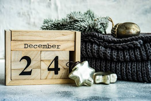 Christmas card concept with wooden calendar, knitted scarf and decoration