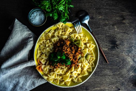 Pasta with carbonara sauce served in a bowl with fresh parsley herb on wooden table with copy space