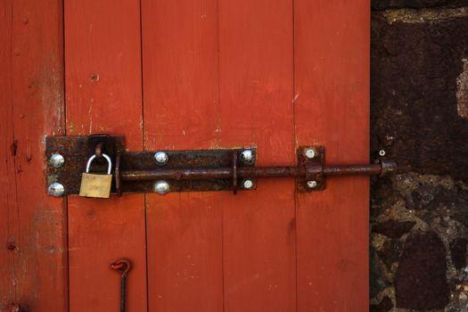 Old rusty lock on a red wooden door