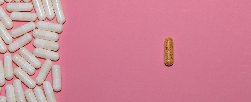 Top view of white pills on one side and a single brown pill on the other side on pink background with copy space. Healthcare, medical and pharmaceutical concept. Banner size.