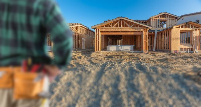 Contractor In Front New House Wood Framing at Construction Site.