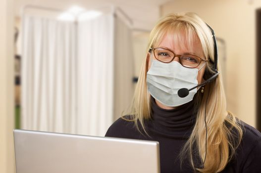 Woman At Medical Office Desk Wearing Face Mask.