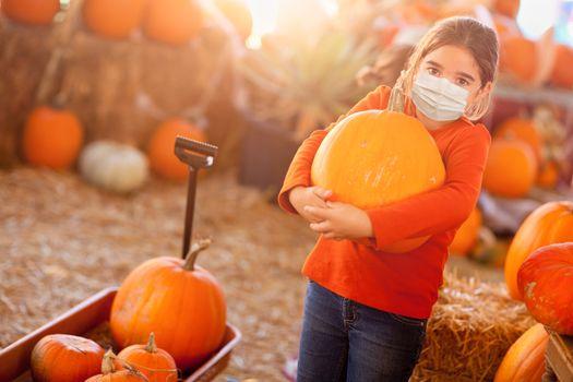 Cute Girl Choosing A Pumpkin At Pumpkin Patch Wearing Medical Face Mask.