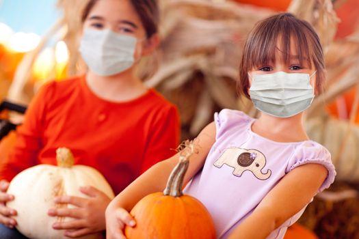 Cute Little Girls Holding Their Pumpkins At A Pumpkin Patch Wearing Medical Face Masks.