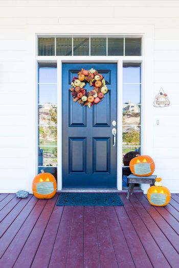 Beautiful House Porch Decorated For Halloween with Pumpkins Wearing Medical Face Masks.