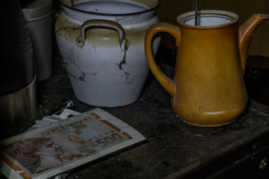 pots with pattern and a bank note in a abandoned kitchen