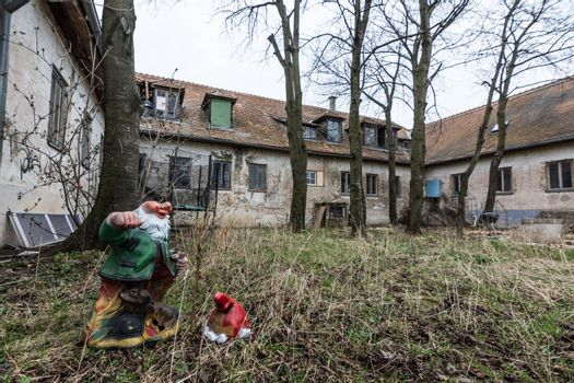 garden gnome with head on the ground at abandoned house with garden