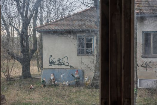 Looking through a window at garden gnomes at an abandoned house