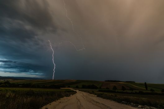 Lightning strike during a thunderstorm in the countryside with a road
