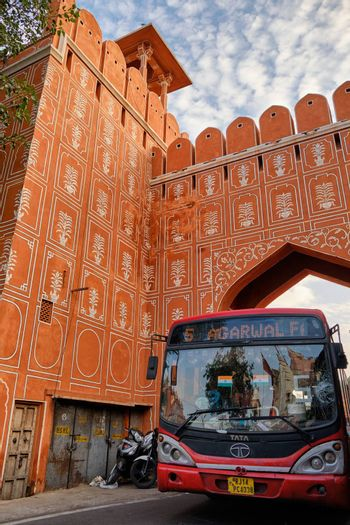 Jaipur, Rajasthan / India - September 28, 2019: Public bus passes through the Chandpole Gate of the walled city of Jaipur, Pink city in India
