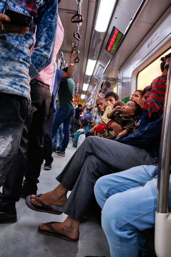 New Delhi / India - September 2019: People sitting in a train carriage of Delhi Metro system