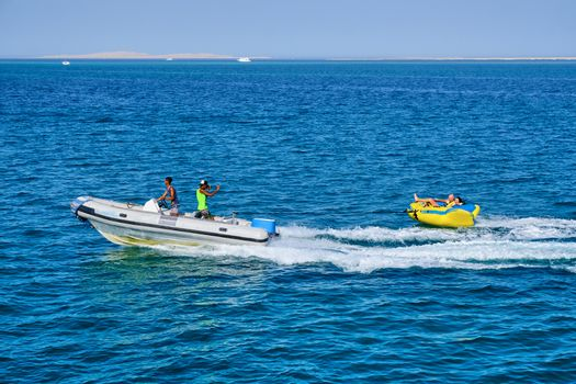 Hurghada / Egypt - May 21, 2019: Tourists riding the inflatable pulled by the speedboat in Hurghada Red sea resort in Egypt