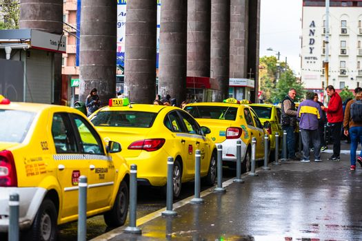 Car in traffic, modern city taxi service. Taxi cars parked at the taxi station in the capital city of Bucharest, Romania, 2020