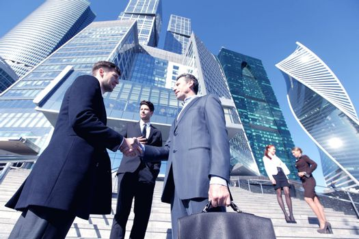 Business people shaking hands, finishing up a meeting outside office