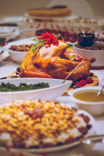 Delicious Stuffed Turkey in the Center of the Table. Tasty Meal for Thanksgiving Day. Traditional American Family Holiday. Festive Dinner at Home.