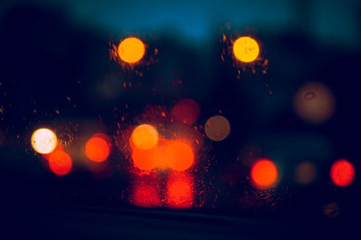 Blurry Lights of Cars Visible Through the Glass of a Car on a Rainy Night. Abstract Background