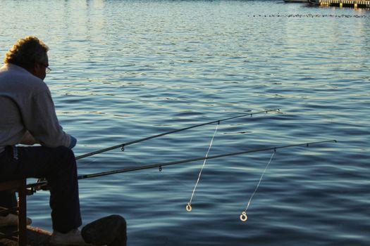 Santa Pola, Spain-December 4, 2017: Man fishing in the port of Santa Pola in the afternoon