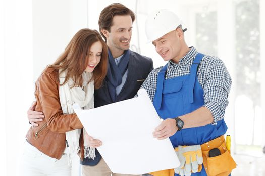 Foreman showing house design construction plan to a happy young couple new house real estate concept