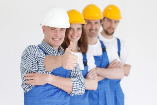 Team of happy workers in uniform ready to work, man showing thumb up sign