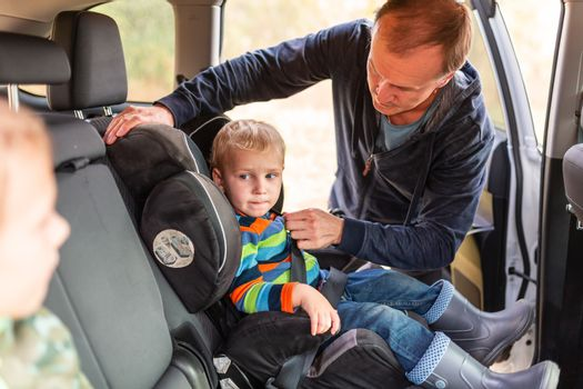 Father fastening safety belt for his baby boy in his car seat.