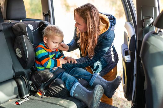 Mother fastening safety belt for her baby boy in his car seat.