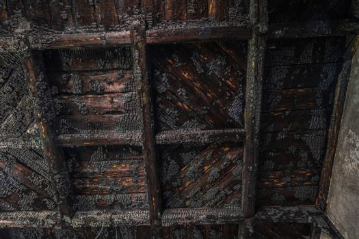 Charred wooden ceiling after a fire from a forest house