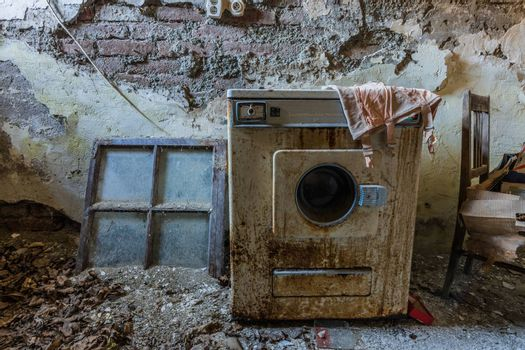 Old rusty washing machine in an abandoned hotel