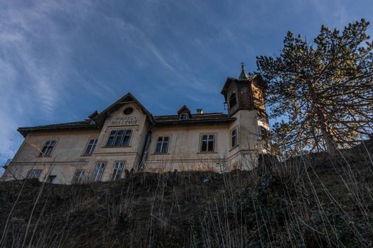 Old abandoned hotel on top of a mountain with blue sky