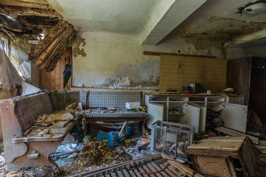 dilapidated kitchen with bench and boxes in a house