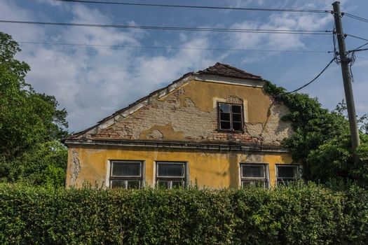 abandoned old house with hedge and electricity pylons