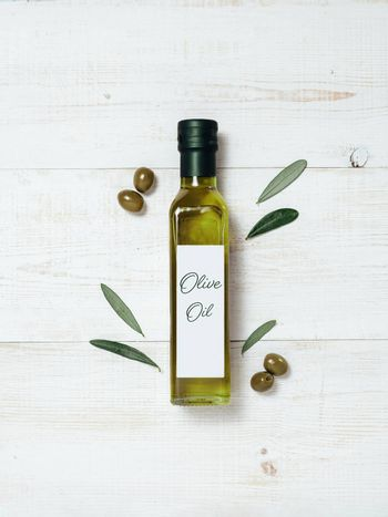 Olive oil glass bottle mock up. Top view of green glass bottle with extra virgin olive oil on white wooden background with green olives and fresh green olive tree leaves. Vertical. Copy space.
