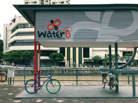 Bicycle parked at Water B ticketing kiosk for Singapore River Cruise by the river in Singapore city.  It is a good way to explore many iconic landmarks of Singapore city.