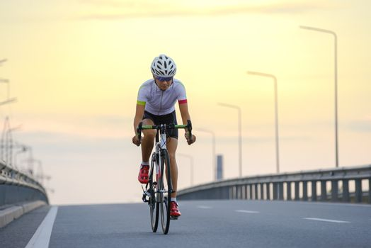 Young Woman Cyclist Riding Bike on the Free Road at Sunset. Adventure, Travel, Healthy Lifestyle and Sport Concept.