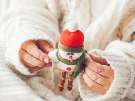 Kid with felt decorative snowman for Christmas tree. Boy in cable-knit oversized sweater. Cozy outfit for snuggle weather. Funny character with red Santa Claus hat. Winter holiday spirit. New year.