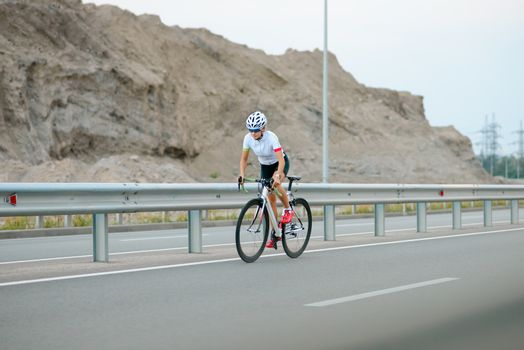 Young Woman Cyclist Riding Road Bike in the Mountains. Adventure, Travel, Healthy Lifestyle and Sport Concept.