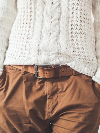 Woman in cable-knit white sweater with Scandinavian patter and brown chinos trousers with leather belt. Casual clothes for snuggle weather. Modern urban fashion.