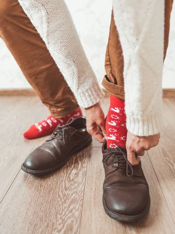 Young man in chinos trousers and bright red socks with reindeers on them is ready to wear suede shoes. Scandinavian pattern. Winter holiday spirit. Casual outfit for New Year and Christmas celebration.