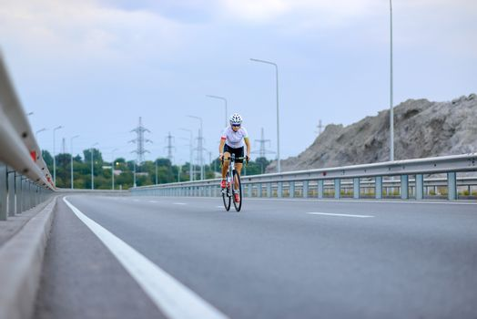 Young Woman Cyclist Riding Bike on the Free Road in the Mountains. Adventure, Travel, Healthy Lifestyle and Sport Concept.