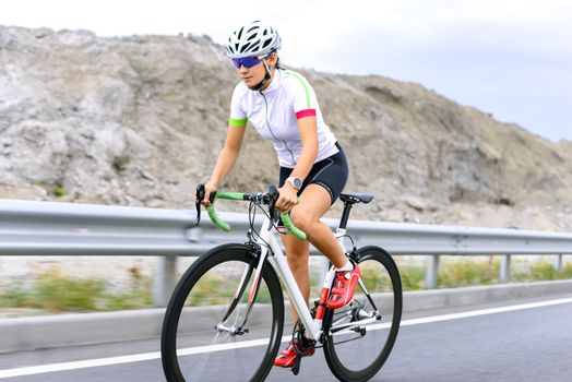 Young Woman Cyclist Riding Bike on the Mountain Road. Adventure, Travel, Healthy Lifestyle and Sport Concept.