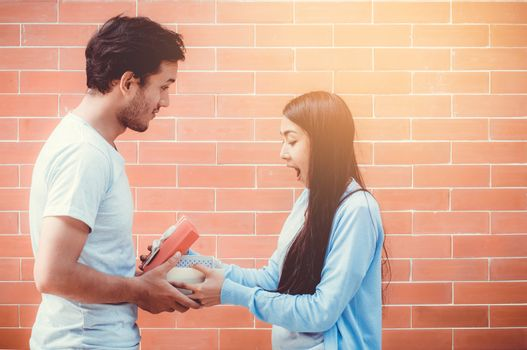 Asian couple young man giving gift box to woman outdoors,  relationship with celebration birthday of boyfriend and girlfriend with happy.