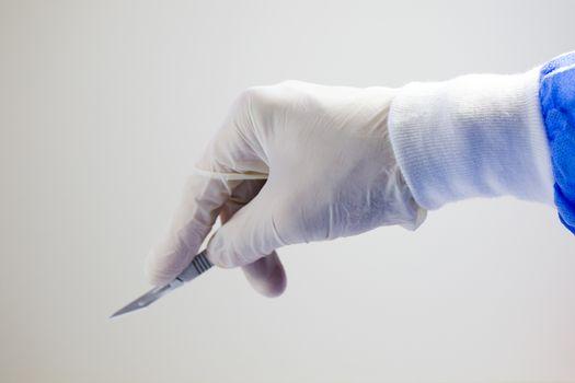 Surgery knife holding on the white background, studio shot. Operation equipment.