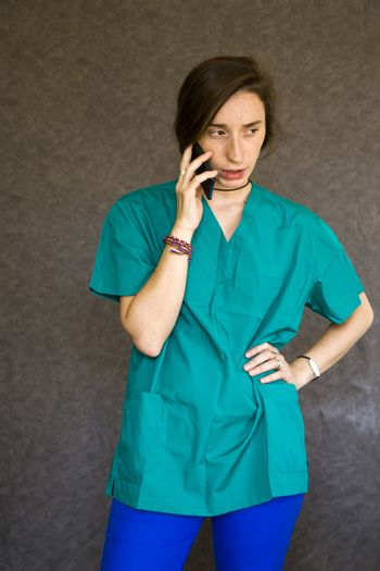 Woman portrait in medical nurse and doctors uniform on the gray background, woman talking on the mobile phone